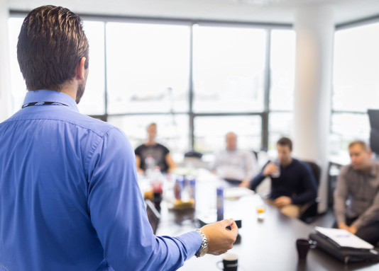 man presenting to co-workers at a meeting