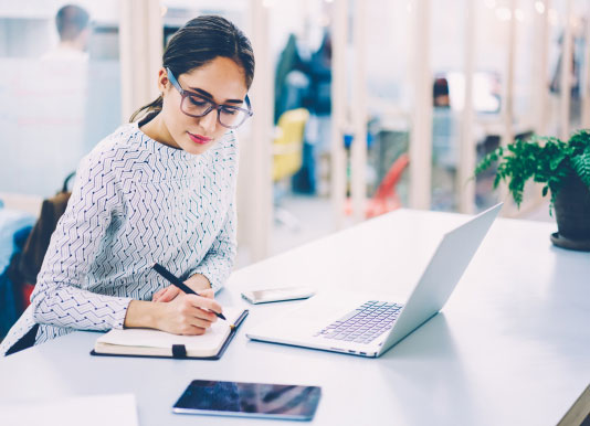 woman with glasses taking notes from a computer