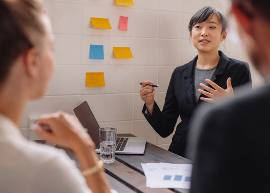 woman explaining to co-workers data findings
