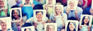 diverse group of people holding tablets in front of their faces with their pictures on the back