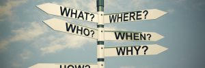 street sign pointing in different directions marked as what, where, who, when, why and how