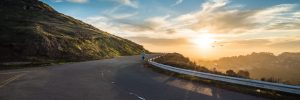 mountainous highway picture with someone jogging towards the sunset