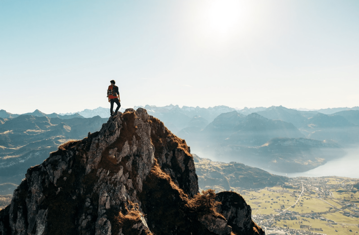 A hiker atop a mountain looking out at other mountains and lakes